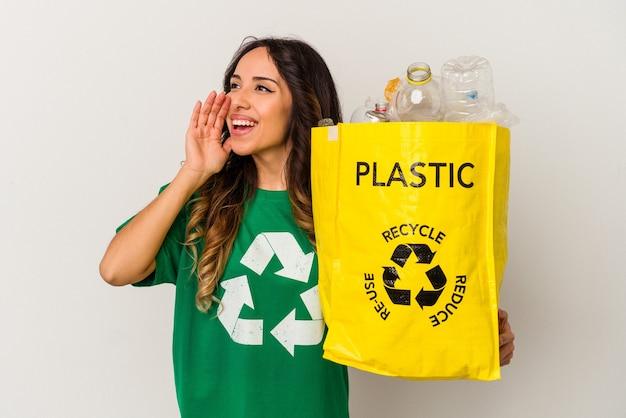 Jonge mexicaanse vrouw recycling plastic geïsoleerd op een witte achtergrond schreeuwen en houden palm in de buurt van geopende mond.