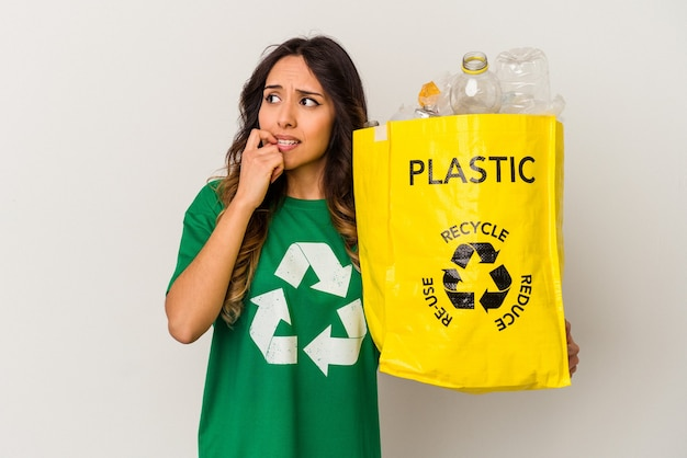 Jonge mexicaanse vrouw recycling plastic geïsoleerd op witte achtergrond ontspannen denken over iets kijken naar een kopie ruimte.