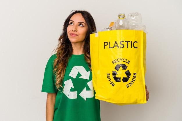 Jonge mexicaanse vrouw recyclingsplastiek dat op witte muur wordt geïsoleerdd die van het bereiken van doelstellingen en doeleinden droomt