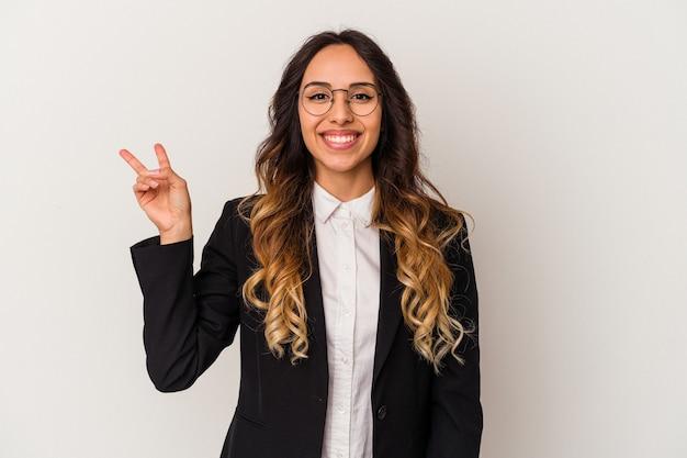 Jonge mexicaanse zakenvrouw geïsoleerd op een witte achtergrond vrolijk en zorgeloos met een vredessymbool met vingers.