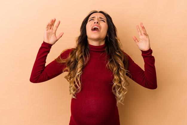 Jonge mexicaanse zwangere vrouw geïsoleerd op beige achtergrond schreeuwen naar de hemel, opzoeken, gefrustreerd.