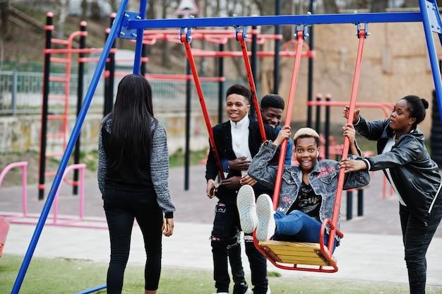 Jonge millennials afrikaanse vrienden op speelplaats, glijbaan en schommel. gelukkige zwarte mensen die samen plezier hebben. generatie z vriendschap concept.