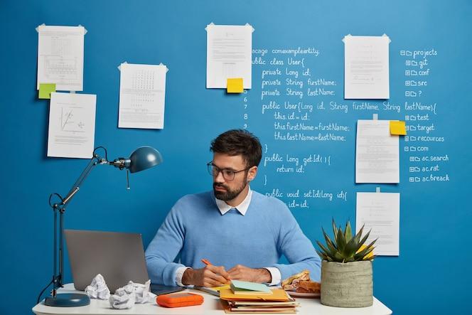 Jonge millenniumstudent zoekt informatie voor huiswerk, schrijft de nodige inhoud op in een leerboek, bereidt een project over it-onderwerp voor