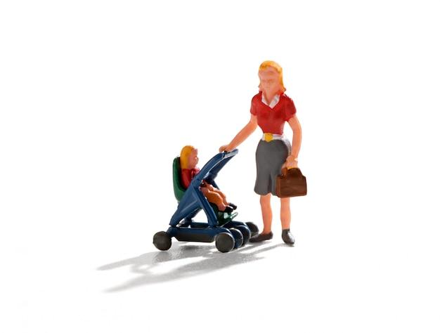 Jonge miniatuurmoeder die een wandelwagen duwt
