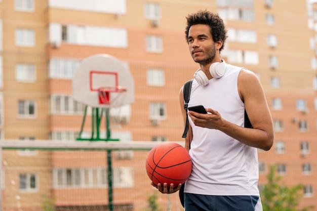 Jonge mixed-race atleet met bal en smartphone texting tijdens pauze op speelplaats in stedelijke omgeving