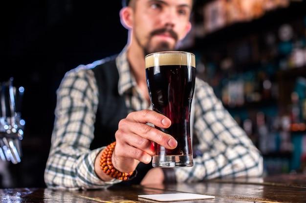 Jonge mixoloog legt de laatste hand aan een drankje terwijl hij naast de toog in de bar staat