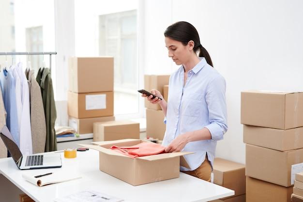 Jonge mobiele vrouw met smartphone foto nemen van gevouwen trui in open doos voor verpakking en verzenden naar de klant