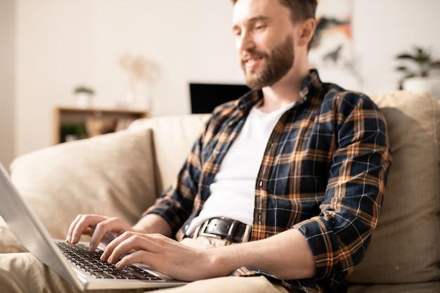 Jonge mobiele zakenman in vrijetijdskleding typen op toetsenbord van laptop tijdens het kijken naar display tijdens netwerk op de bank