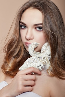 Jonge mode blond meisje met broche vogel sieraden in handen