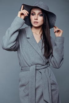 Jonge mode brunette vrouw in grijze jas en hoed