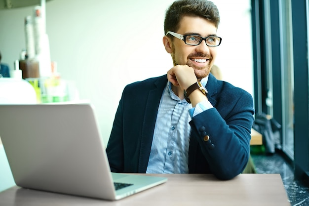 Jonge mode glimlachende hipster mens in het stadscafe tijdens lunchtijd met notitieboekje in kostuum