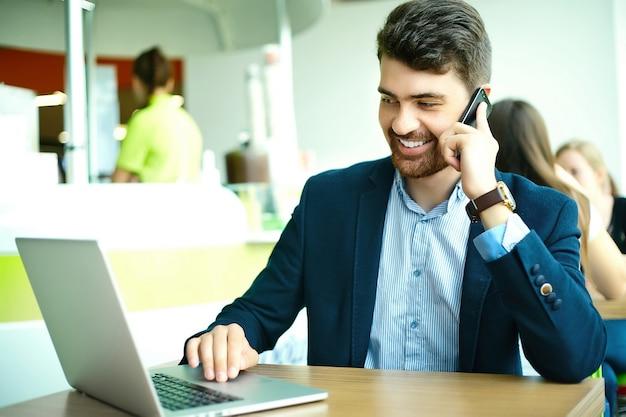 Jonge mode lachende hipster man in het café van de stad tijdens de lunchtijd met laptop in pak spreken op telefoon