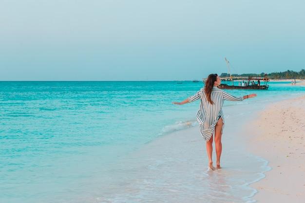 Jonge mode vrouw in groene jurk op het strand