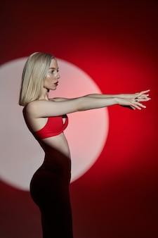 Jonge mode vrouw in rode lingerie ondergoed zwembroek licht en schaduw, gevoelige vrouw poseren in een cirkel van licht