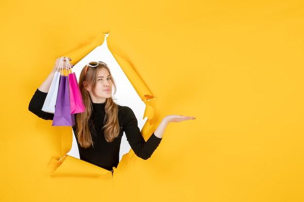 Jonge mode vrouw met boodschappentassen door gescheurd papier gat in de muur