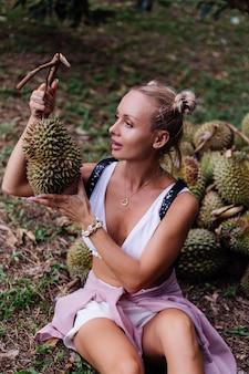 Jonge mode vrouw op een tropisch veld met durian fruit