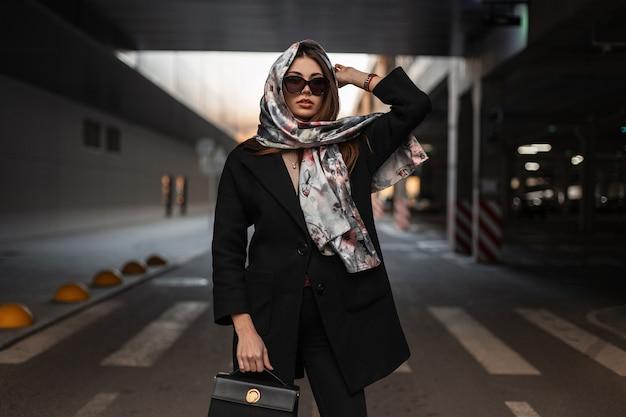 Jonge mode zakenvrouw in stijlvolle zonnebril in een zwarte jas met een modieuze lederen handtas in glamour sjaal poseren in de buurt van parkeerplaats op straat. aantrekkelijk trendy meisje. elegante dame.