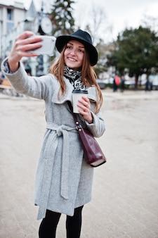 Jonge model meisje in een grijze jas en zwarte hoed met lederen handtas op schouders blijven met plastic kopje koffie