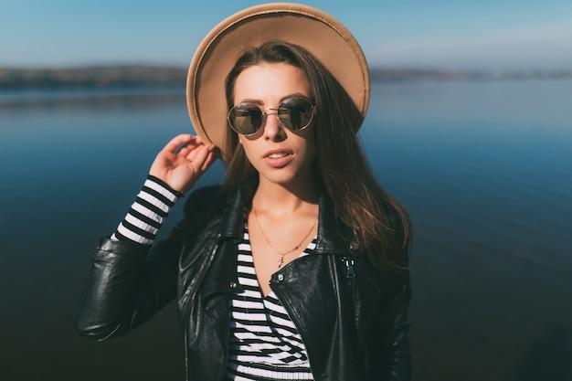 Jonge model meisje vrouw poseren in herfstdag aan de waterkant van het meer gekleed in vrijetijdskleding