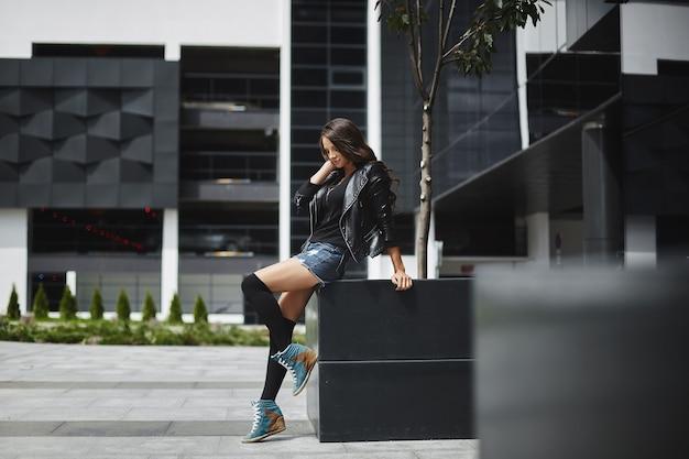 Jonge model vrouw in denim shorts en leren jas poseren op de straat op een zomerdag stad