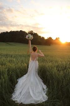 Jonge model vrouw in kant trouwjurk bruids boeket in opgeheven hand houden en poseren met haar rug in het zomer veld op de zonsondergang