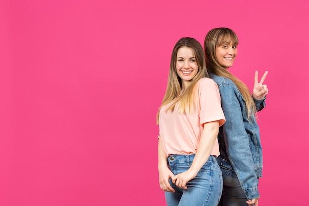 Jonge modellen die met roze achtergrond stellen