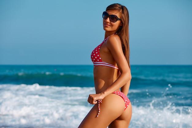 Jonge modelvrouw in badkleding aan de zeekust