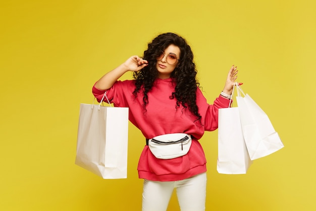Jonge modelvrouw in een roze hoodie en modieuze zonnebril poseren met boodschappentassen op gele achtergrond, geïsoleerd met kopie ruimte