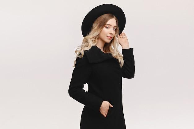Jonge modelvrouw in een zwarte jas en zwarte modieuze hoed die zich voordeed op witte achtergrond, geïsoleerd met exemplaarruimte voor tekst of product