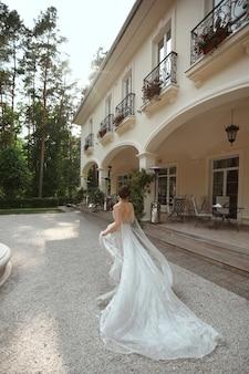 Jonge modelvrouw in kanten trouwjurk ontsnappen aan de huwelijksceremonie. jonge weggelopen bruid in modieuze trouwjurk buitenshuis