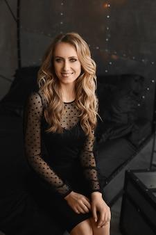 Jonge modelvrouw met avondmake-up in een zwarte cocktailjurk die binnen glimlacht en stelt