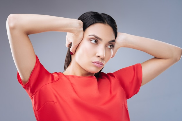 Jonge modelvrouw met rode jurk die zich voordeed op grijze muur