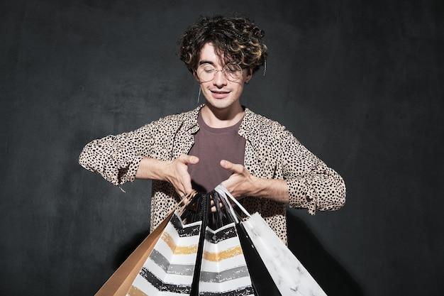 Jonge modeontwerper met boodschappentassen in zijn handen tegen de zwarte achtergrond