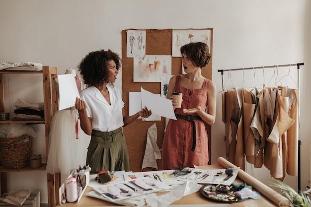 Jonge modeontwerpers kijken geschokte buikspieren ontevreden op kantoor