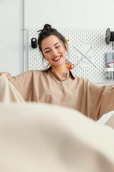 Jonge modeontwerpster die alleen in haar atelier werkt