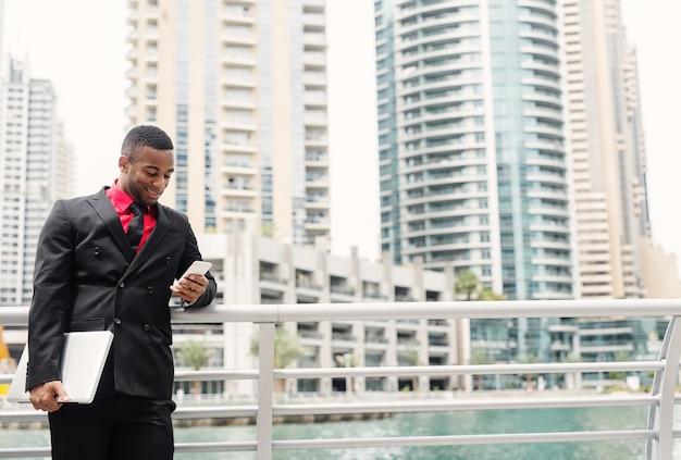 Jonge moderne afro-amerikaanse zakenman leunde op hek in dubai marine terwijl hij met een glimlach naar zijn telefoon keek.