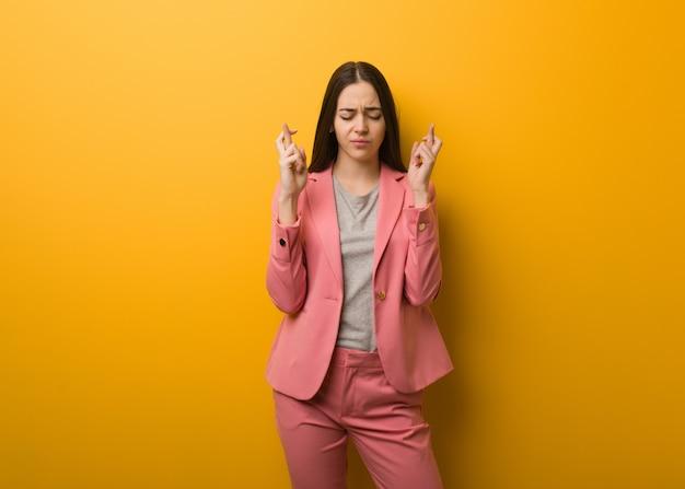 Jonge moderne bedrijfsvrouw die vingers kruist voor het hebben van geluk