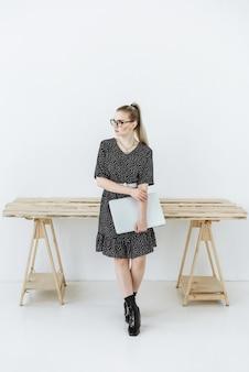 Jonge moderne blonde vrouw in een jurk en bril bij de tafel met een laptop in haar handen