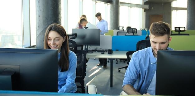 Jonge moderne collega's in slimme vrijetijdskleding die werken terwijl ze tijd op kantoor doorbrengen.
