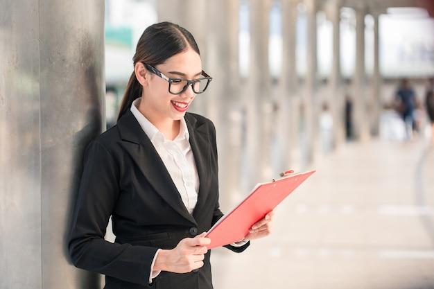 Jonge moderne glimlachende bedrijfsvrouw die kartonnen raad kijkt