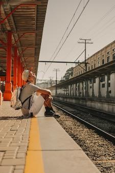 Jonge moderne jongen die door het platform op de trein wachten om aan te komen