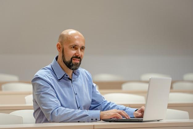 Jonge moderne man op een universitaire lezing die op laptop werkt