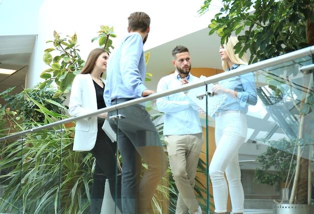 Jonge moderne mensen in slimme vrijetijdskleding die een brainstormvergadering hebben terwijl ze achter de glazen wand op kantoor staan.