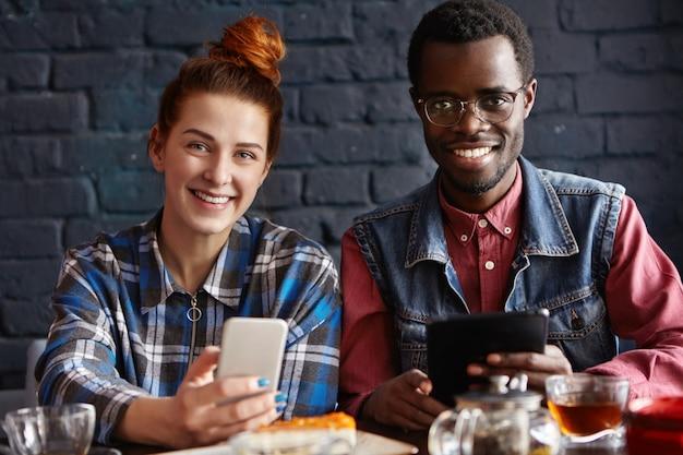 Jonge moderne mensen met elektronische apparaten plezier tijdens koffiepauze binnenshuis in café.