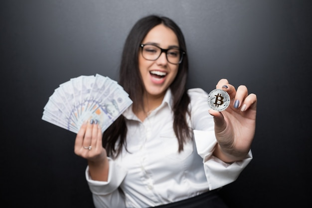 Jonge moderne succesvolle bedrijfsvrouw die een gouden bitcoin en contant gelddollar houdt die op zwarte muur wordt geïsoleerd