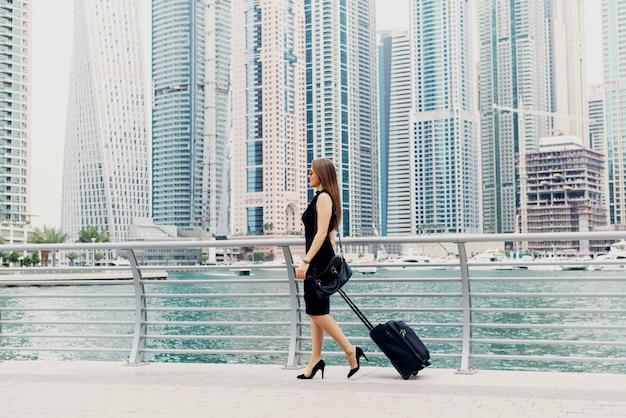 Jonge moderne vertrouwen zakenvrouw trekken een koffer in een dubai marine. een nieuwe baan beginnen in een grote stad.
