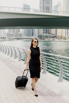 Jonge moderne vertrouwen zakenvrouw trekken een koffer in een dubai marine.