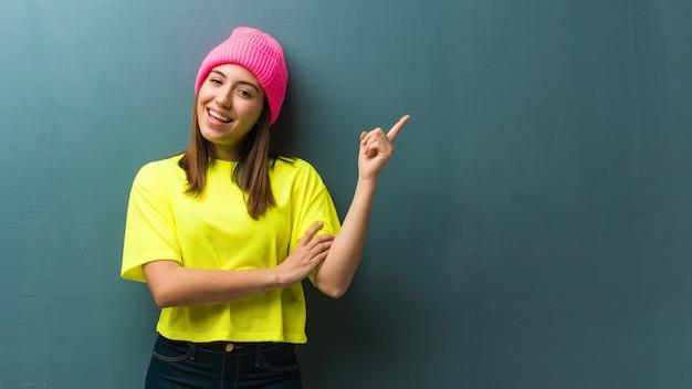 Jonge moderne vrouw die aan de kant met vinger richt