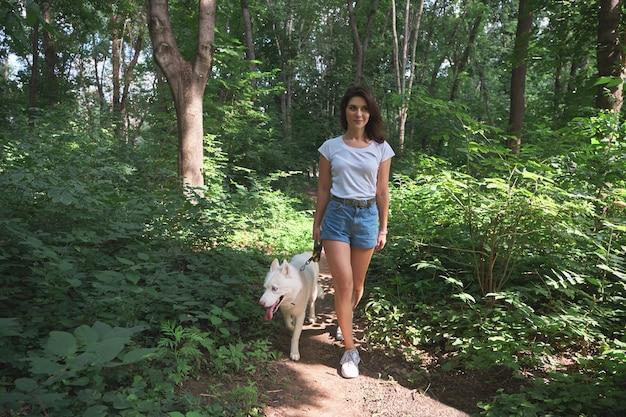 Jonge moderne vrouw die met een hond in het de zomerlandschap wandelt. vriendschap, mensen, dieren