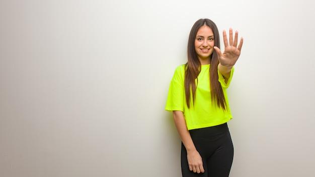 Jonge moderne vrouw die nummer vijf toont